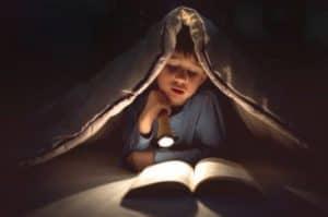 Kid reading with flashlight